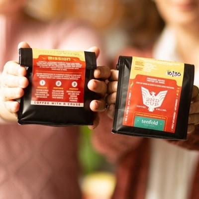 Hands holding bags of A 2nd Cup coffee beans
